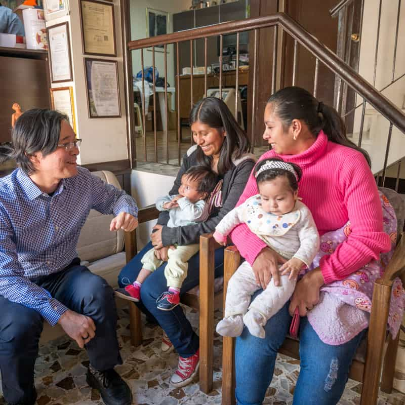 Solidarity bridge: Maryknoll Father Dae Kim welcomes Roxana Mamani (left) and her baby Ailee, and Ariane Castro and her daughter Mariana at the office of Puente de Solidaridad. (Nile Sprague/Bolivia)