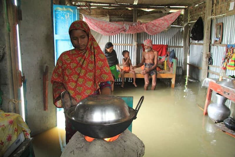 Bangladesh floods: Woman cooks food inside a flood-affected house in the Nageswari area of Kurigram district on July 14. (Liton Das, UCA News)