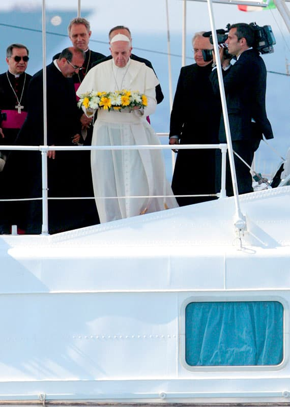 Pope Francis tosses a wreath of flowers into the Mediterranean Sea off the Italian island of Lampedusa in this July 8, 2013, file photo. The pope threw a wreath to honor the memory of immigrants who have died trying to cross from Africa to reach a new life in Europe. (CNS photo/pool)