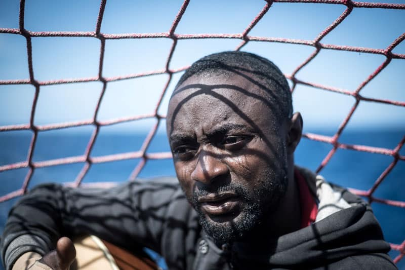 A migrant is seen in a file photo holding his guitar aboard the Sea Watch 3 German charity ship off the coast of Lampedusa, Italy. (CNS photo/Nick Jaussi, Sea-Watch via Reuters)