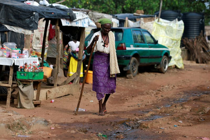 An internally displaced Nigerian woman walks with the aid of a stick in late June at a camp in Abuja. (CNS photo/Afolabi Sotunde, Reuters)