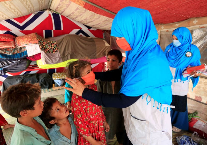 protect refugees: A UNICEF worker helps an internally displaced Afghan girl put on a protective mask at a makeshift camp in Jalalabad in late June during the COVID-19 pandemic. (CNS photo/Parwiz, Reuters)