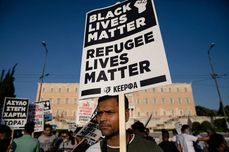 """A man holds a placard reading """"Black Lives Matter, Refugee Lives Matter"""" during a demonstration outside the Greek parliament in Athens June 26, 2020. (CNS photo/Alkis Konstantinidis, Reuters)"""