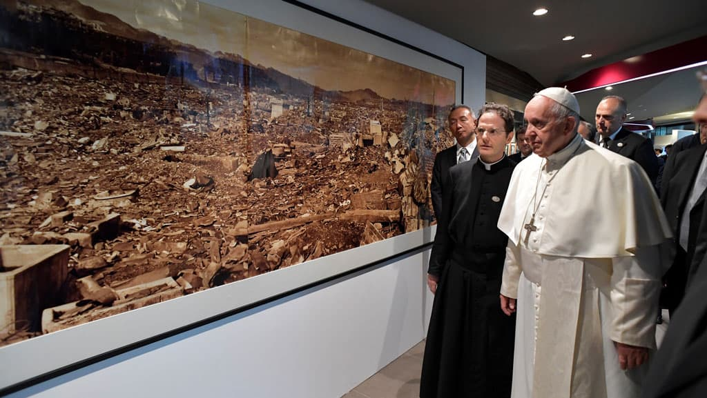 Pope Francis walks by a photo showing the destruction created by an atomic bomb during his Nov. 26, 2019, visit to the Jesuit-run Sophia University in Tokyo. (CNS photo/Vatican Media via Reuters)