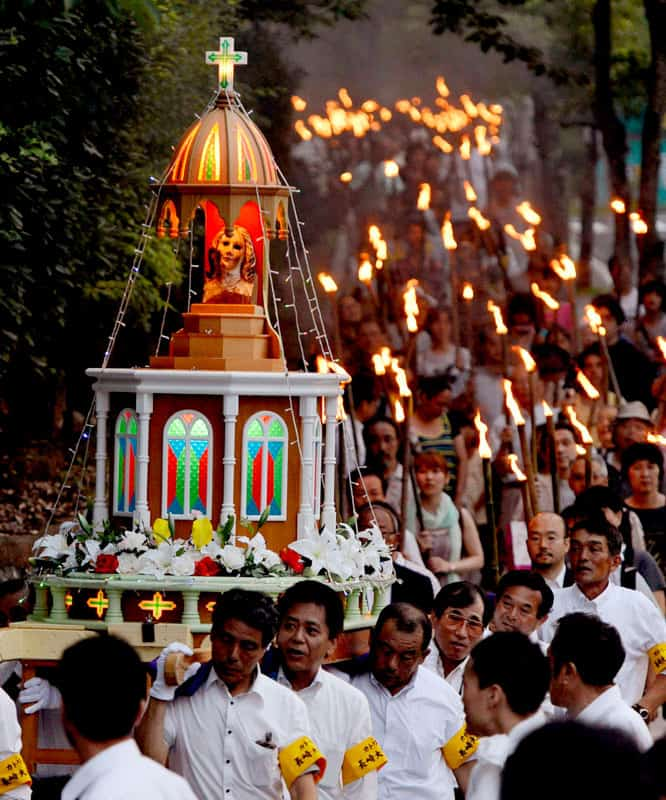 People carry the remains of a statue of Mary that survived the atomic blast over Nagasaki, Japan, as they march through the streets of the city Aug. 9, 2012. (CNS photo/Kyodo, Reuters)