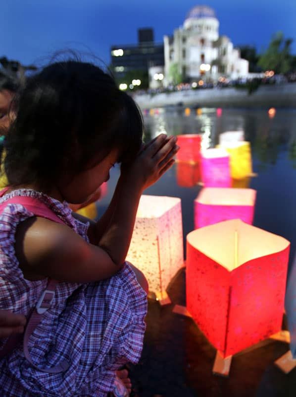 A girl prays after releasing a paper lantern on the Motoyasu River facing the gutted Atomic Bomb Dome in Hiroshima, Japan, Aug 6, 2020, the 75th anniversary of the U.S. dropping the atomic bomb on Hiroshima. (CNS photo/Yuriko Nakao, Reuters)