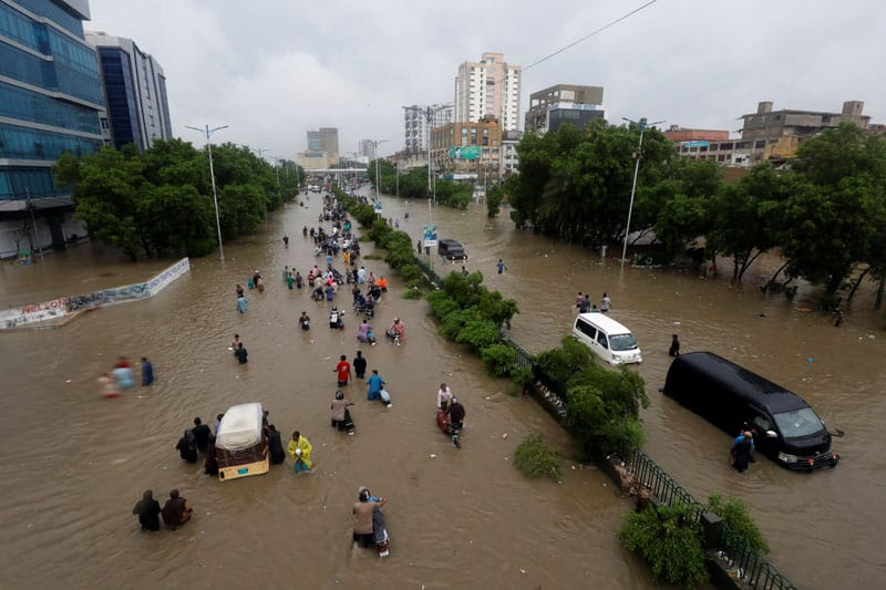 People wade through the floodwaters in Karachi, Pakistan, Aug. 27, 2020, following heavy rains. (CNS photo/Akhtar Soomro, Reuters)