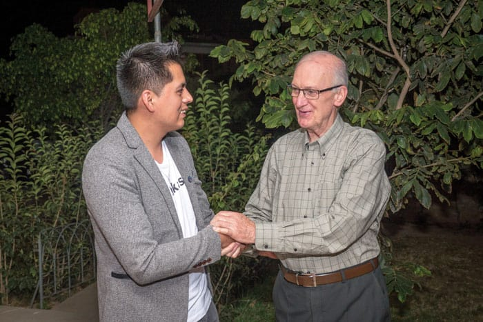 Father Chapin shakes hands with Ronald Albarez, a young parishioner and psychologist, who is helping other parishioners deal with COVID-19. (Nile Sprague/Bolivia)
