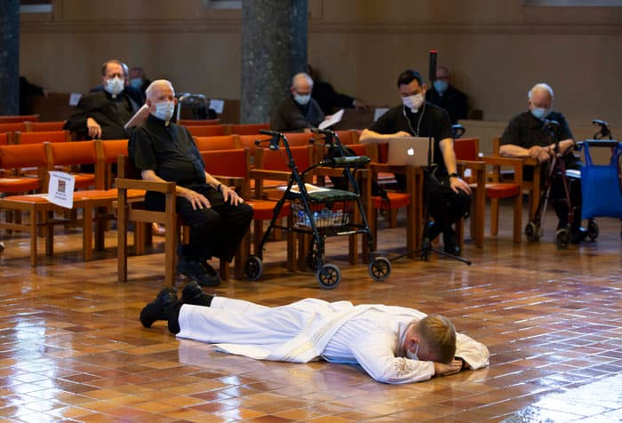 Maryknoll Father Gregory McPhee is prostrated, during the Mass of his ordination to the priesthood, while other Maryknoll priests recite the Litany of Supplication, maintaining social distance due to COVID-19. (Octavio Duran/U.S.)