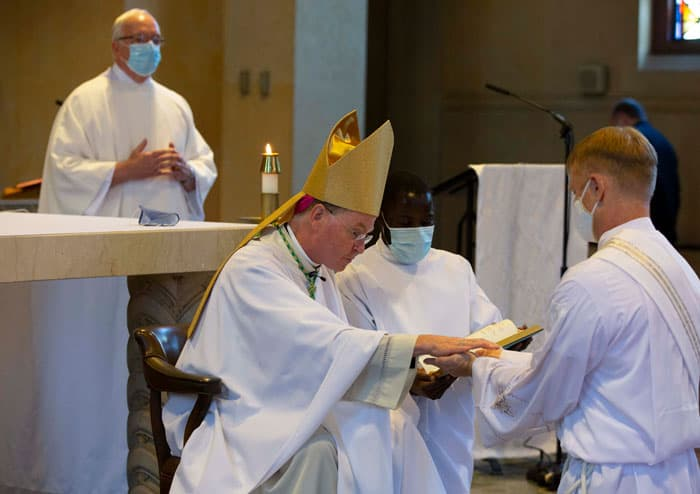 Bishop Edmund J. Whalen anoints McPhee's hands with oil at the young man's ordination to the Maryknoll missionary priesthood. (Octavio Duran/U.S.)