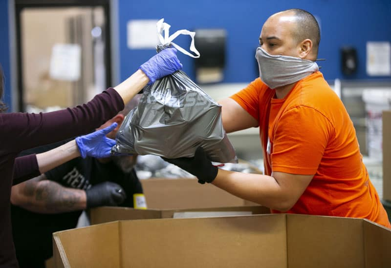 Adam Cadena, a United Food Bank volunteer, takes emergency food bags and places them in boxes at the United Food Bank warehouse in Mesa, Arizona, in this April 16, 2020, file photo. In an interview, Cardinal Pietro Parolin, Vatican secretary of state, said putting a priority on the human person is needed for economic recovery from the coronavirus pandemic. (CNS photo/David Wallace, Reuters)