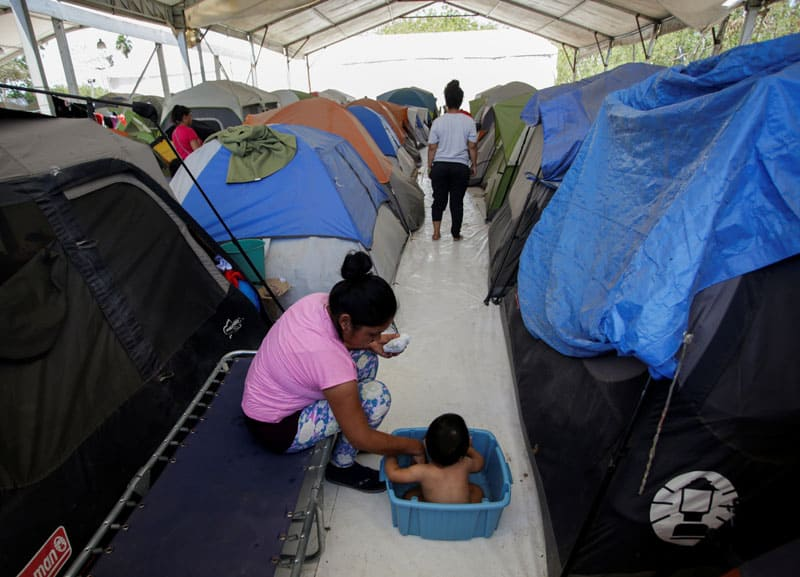 A migrant woman bathes her son outside their tent at a migrant encampment in Matamoros, Mexico, April 30, 2020, where more than 2,000 people live while seeking asylum in the U.S, as the spread of the coronavirus continues. (CNS photo/Daniel Becerril, Reuters)