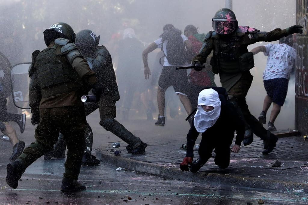 Demonstrators and riot police clash during a protest against Chile's government in Santiago Oct. 18, 2020, the one-year anniversary of the protests and riots that rocked the capital. The demonstrations occurred a week before a referendum on whether to ditch a dictatorship-era constitution. (CNS/Ivan Alvarado, Reuters)
