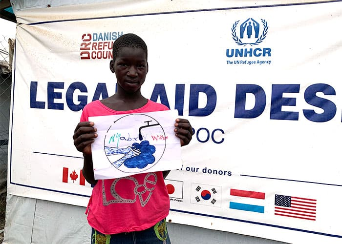 At a U.N. project on COVID-19 awareness, a youth shows her drawing of the need for handwashing to prevent the spread of the virus. (Courtesy of Michael Bassano/South Sudan)