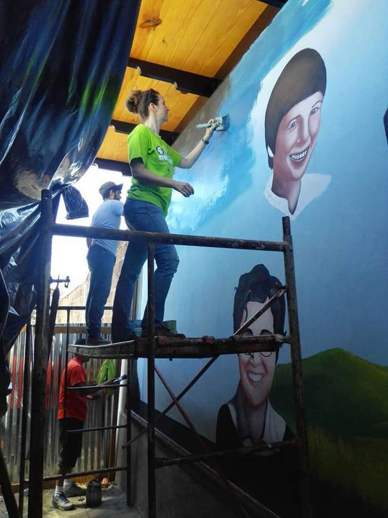 Melissa Altman of the Maryknoll Lay Missioners paints the sky in a mural Dec. 11, 2016, in Zaragoza, El Salvador, featuring the four U.S. Catholic women assassinated in the Central American country Dec. 2, 1980. Four decades after the killings, Altman, who serves in mission with her family in El Salvador, said the women's example of faith continues to inspire her to continue their work. (CNS/Fatima Pacas for International Partners in Mission via of Melissa Altman of Maryknoll Lay Missioners)