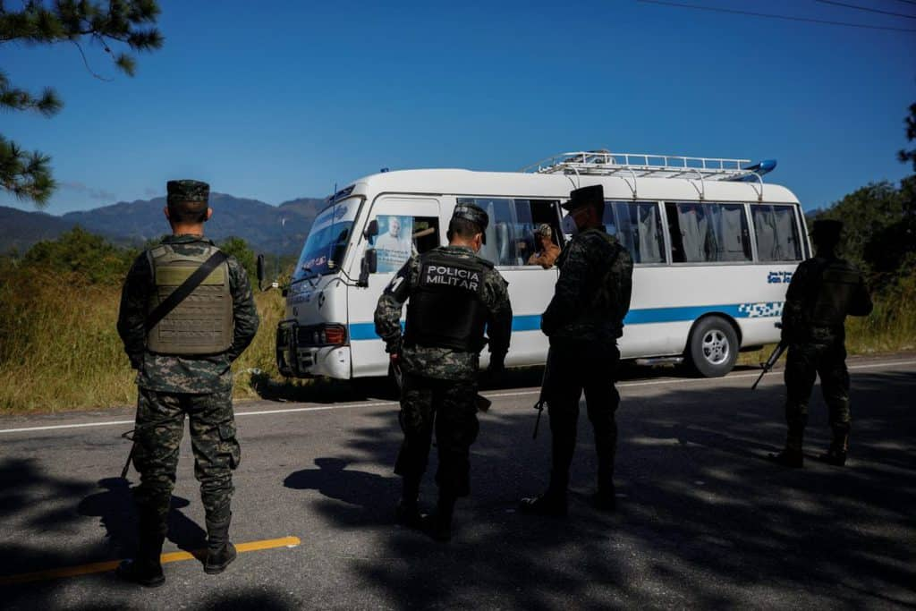 Members of Honduran security forces stand in front of a bus at a check point in Ocotepeque, Honduras, Dec. 10, 2020. The bus is carrying people taking part in a new caravan of migrants, set to head to the United States. (CNS/Jose Cabezas, Reuters)