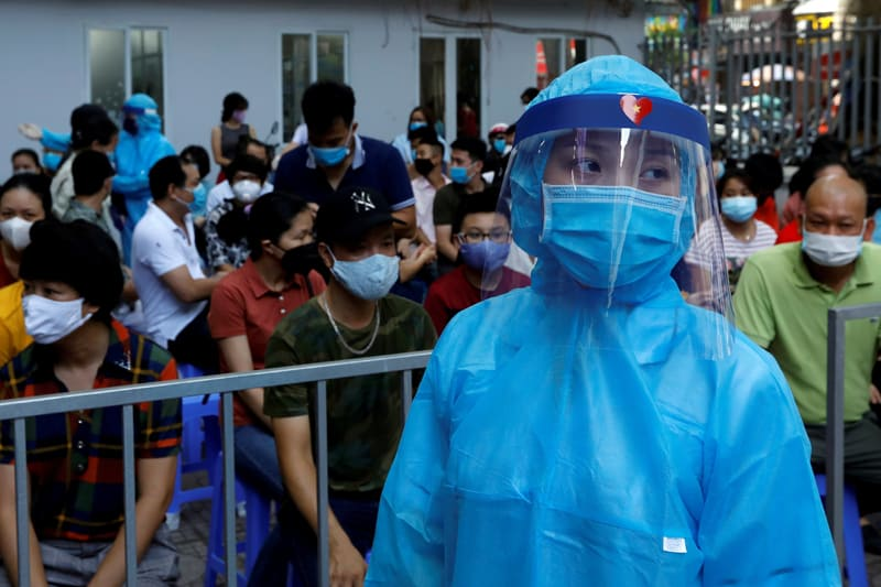 A health care worker in Hanoi, Vietnam, wears a protective suit Aug. 10, 2020, while other people wait in line to be tested for COVID-19. Vietnamese government officials have praised the country's Catholics for their contributions in addressing the coronavirus pandemic. (CNS photo/Kham, Reuters)
