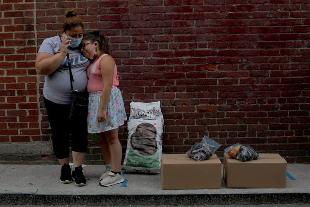 Sandra Cruz of Chelsea, Mass., waits for a ride with her daughter after picking up free groceries from a food pantry July 22, 2020. Cruz lost her job because of the coronavirus pandemic, fell four months behind on her rent and was fearing eviction. (CNS photo/Brian Snyder, Reuters)