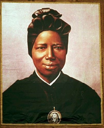 A tapestry of St. Josephine Bakhita, an African slave who died in 1947, hangs from the facade of St. Peter's Basilica during her canonization in 2000 at the Vatican. Pope Francis released a video message marking the International Day of Prayer and Awareness against Human Trafficking, which is celebrated on the Feb. 8 feast of St. Bakhita. (CNS photo/L'Osservatore Romano via Reuters)