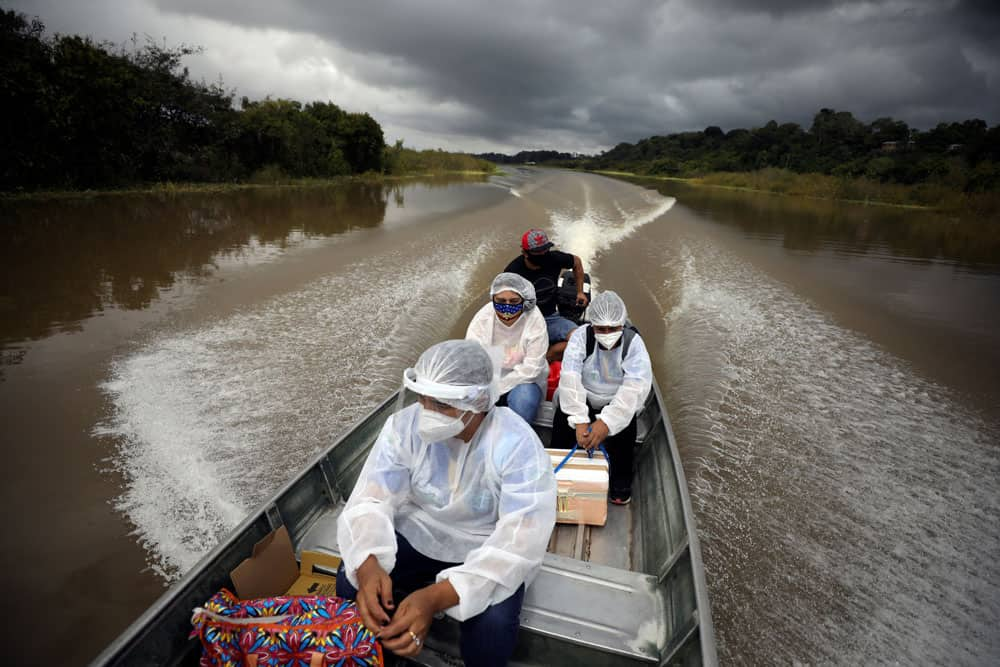 Municipal health workers travel on a boat along the Solimoes River to apply the Oxford-AstraZeneca vaccine for COVID-19 to the residents who live along the river in Manacapuru, Amazonas state, Brazil, Feb. 1, 2021. (CNS photo/Bruno Kelly, Reuters)
