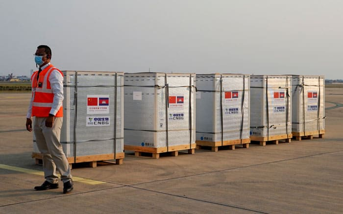 Asia Ocenia roundup A worker stands next to the shipment of 600,000 doses of COVID-19 vaccines at Cambodia's Phnom Penh International Airport Feb. 7, 2021. The vaccines were donated by China. (CNS photo/Cindy Liu, Reuters)
