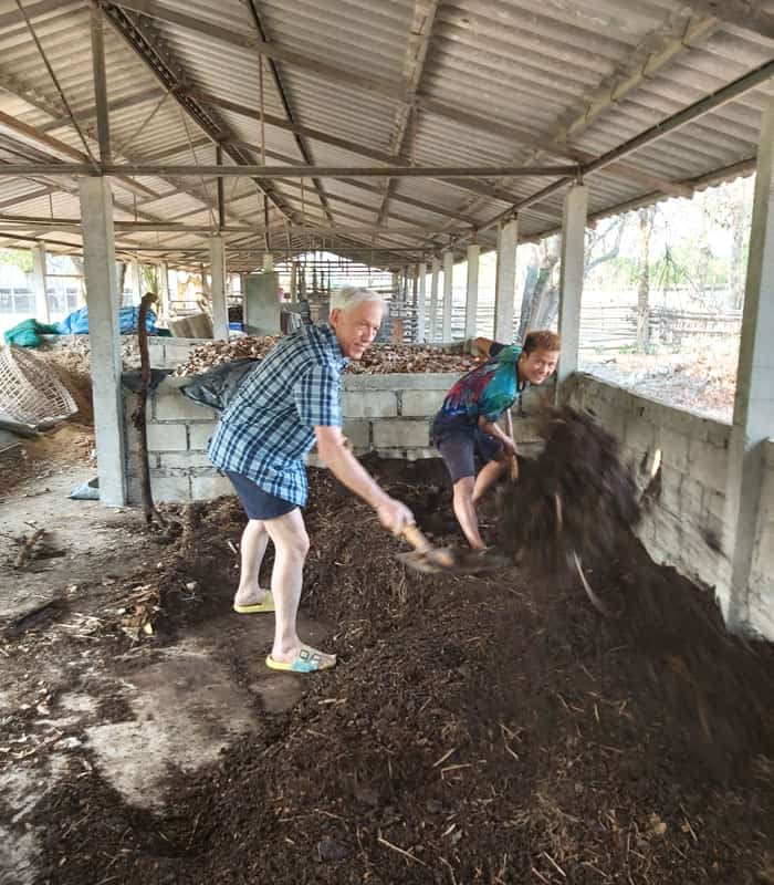 Father Radice (left) and Somboon, a student of the Lahu ethnic group, work on composting. (Courtesy of Lawrence Radice/Thailand)