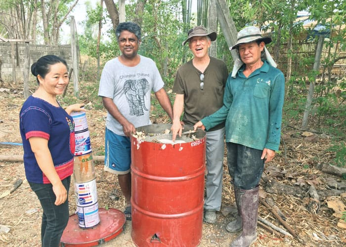 Staff members of RTRC (l. to r.) Ms. Phut, Mr. Sornchai, Father Radice and Mr. Manut make biochar by burning organic waste material. (Courtesy of Lawrence Radice/Thailand)