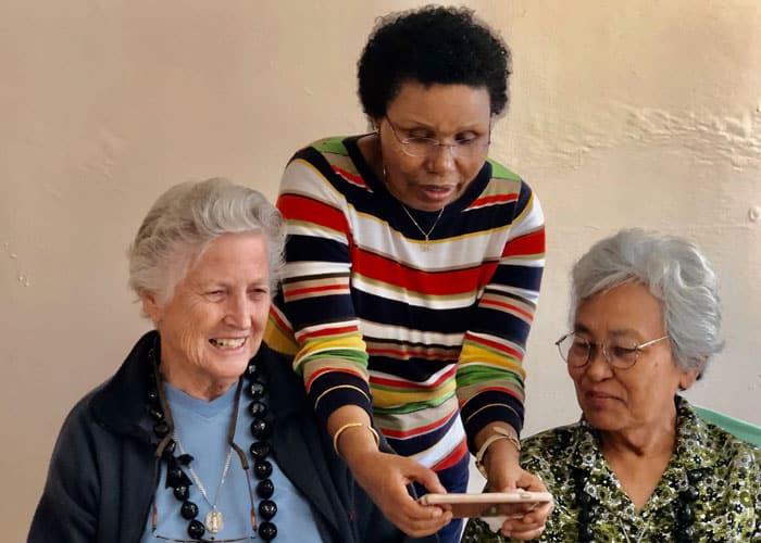 Sister Bitrina Kirway demonstrates the marvels of the smartphone to her Maryknoll Sister companions Ardis Kremer (left) and Rosalinda Barrozo. (Courtesy of the Maryknoll Sisters)