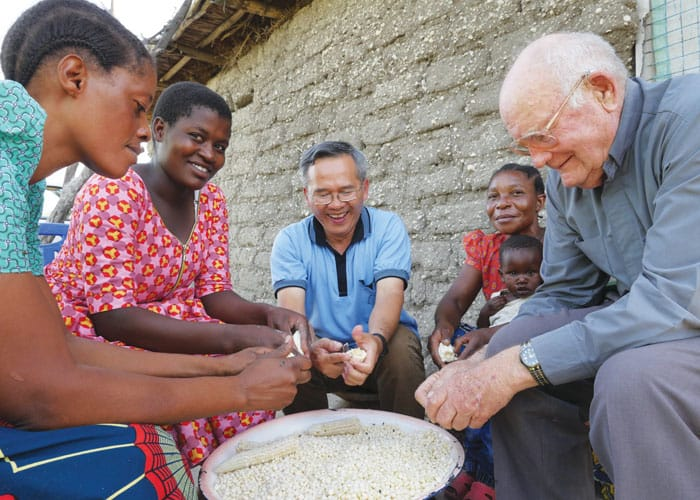 Maryknoll Father Hung Dinh, center, and Father John Lange help a family in Ndoleleji parish remove dried corn kernels from their cobs in Shinyanga Diocese in Tanzania.