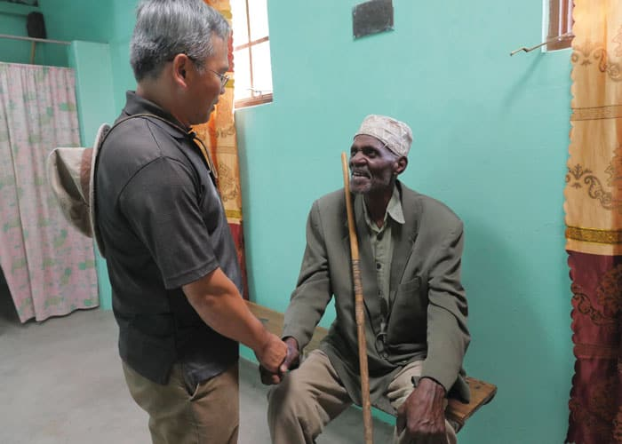 Father Dinh greets a local man at the medical clinic he helps support in Ndoleleji parish.
