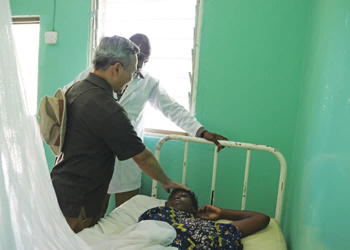 Father Dinh blesses an ailing woman while making rounds with a clinical officer at the Ndoleleji medical clinic and dispensary that treats about 40 patients a week.