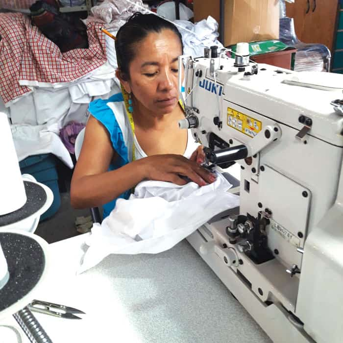 Esmeralda sews buttons on school uniform shirts at Acomujerza cooperative, where she has worked for 15 years and is now a head seamstress. (Ana Morales/El Salvador)