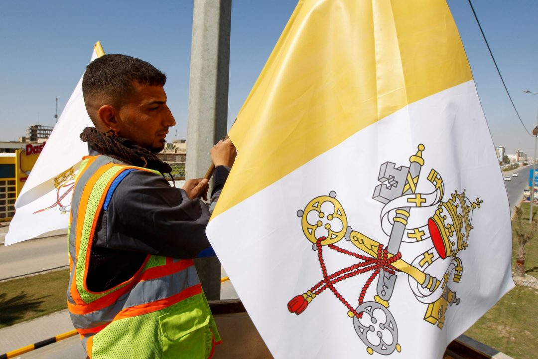 A worker hangs the Vatican flag on a utility pole in Najaf, Iraq, Feb. 27, 2021. Pope Francis plans to visit Iraq March 5-8. (CNS photo/Alaa Al-Marjani, Reuters)
