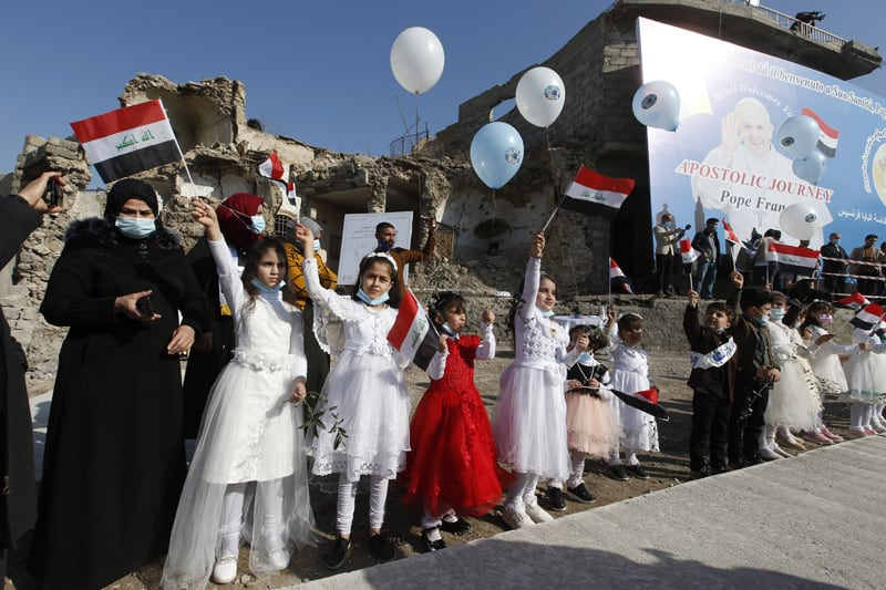 Children wave Iraqi flags before Pope Francis' arrival for a memorial prayer for the victims of the war at Hosh al-Bieaa (church square) in Mosul, Iraq, March 7, 2021. (CNS photo/Paul Haring)