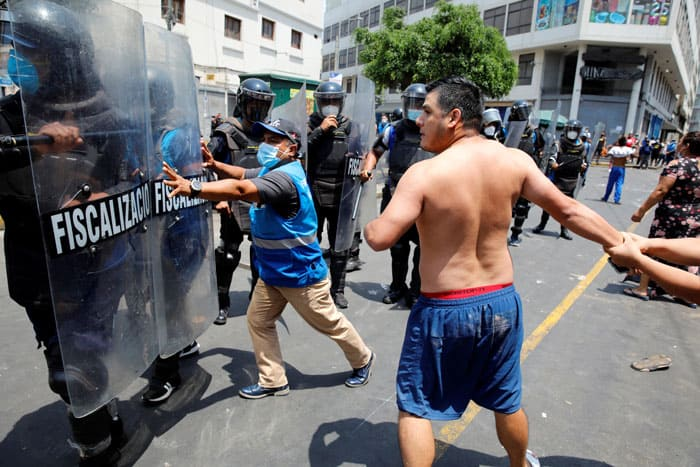 Protesters and street vendors argue with riot police over new government restrictions in Lima, Peru, Feb. 1, 2021, during the COVID-19 pandemic. (CNS photo/Sebastian Castaneda, Reuters)
