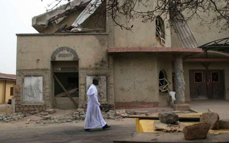 A Catholic Priest walks in front of damaged St. Leo the Great Catholic Church in Enugu State, Nigeria. Credit: Aid to the Church in Need (ACN)