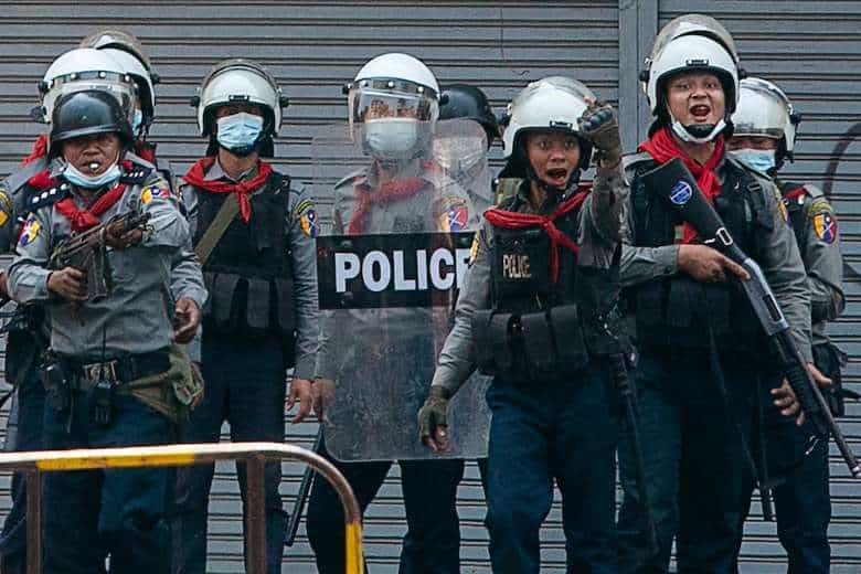 Police gesture toward protesters as security forces crack down on demonstrations against the military coup in Yangon on Feb. 28. At least 18 protesters were shot dead. (Photo: Sai Aung Main/AFP)