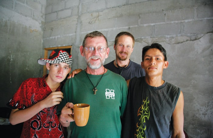 Father Thomas Goekler pauses for a coffee break with two local youths and a visiting doctor, Brandon Stark of Chico, California, in a 2006 photo in Chamelecón.(Sean Sprague/Honduras)