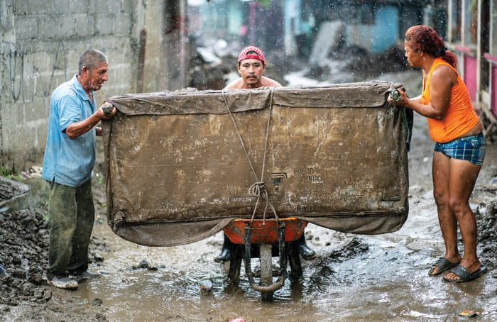 Residents move a reclaimed couch during a torrential rainstorm in Chamelecón, a neighborhood of San Pedro Sula, Honduras. They hope to clean and resell it to those who lost everything during Hurricanes Eta and Iota last year. (Gregg Brekke/Honduras)