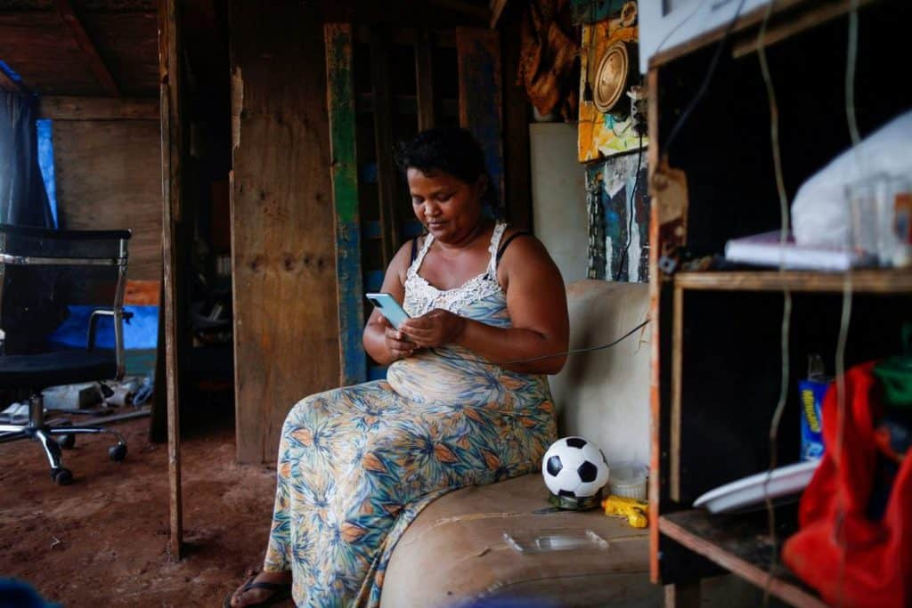 Tatiana Araujo de Sirqueira, 33, uses a cell phone in her home set up on land near Planalto Palace during the coronavirus pandemic in Brasília, Brazil, March 3, 2021. In a message to participants of the World Bank Group and International Monetary Fund 2021 virtual spring meetings, Pope Francis called for debt relief and said poor countries cannot be expected to recover from the current financial crisis if the world returns to an economic model in which a small minority of people owns half of the world's wealth. (CNS photo/Adriano Machado, Reuters)