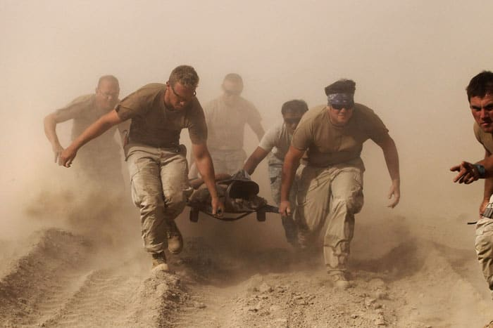 Members of the Navy in Kandahar province in southern Afghanistan carry a comrade wounded by an explosion to a medevac helicopter Oct. 2, 2010. (CNS photo/Finbarr O'Reilly, Reuters)