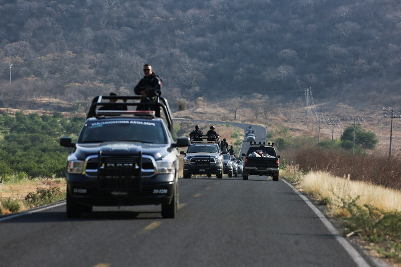 A state police convoy patrols a road near Aguililla, Mexico, April 23, 2021, after a visit from Archbishop Franco Coppola, the apostolic nuncio to Mexico. Drug cartels have battled each other and blocked highways in the town, leaving residents unable to travel freely and causing shortages of everything from food to fuel. (CNS photo/Alan Ortega, Reuters)