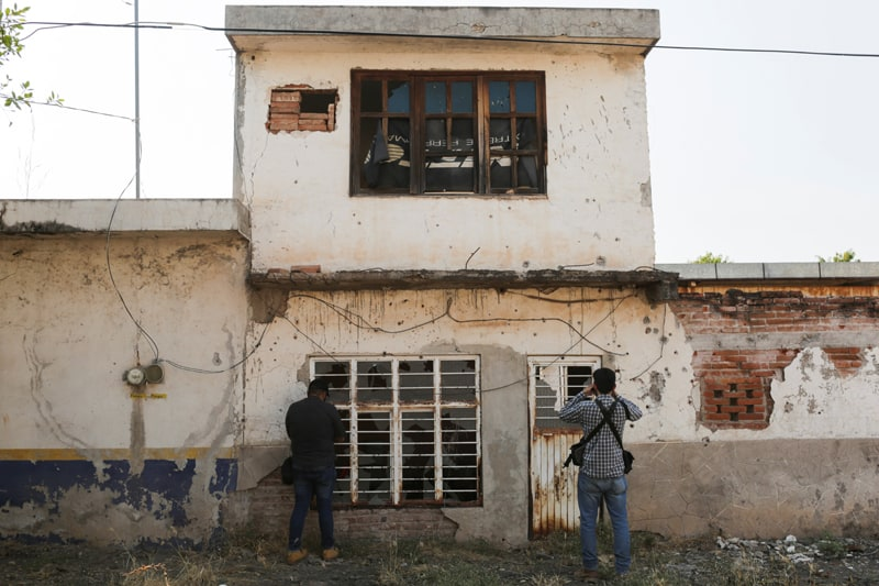 Photographers take pictures of the bullet-riddled front of an abandoned house near Aguililla, Mexico, April 23, 2021. Drug cartels have battled each other and blocked highways in the town, leaving residents unable to travel freely and causing shortages of everything from food to fuel. (CNS photo/Alan Ortega, Reuters)