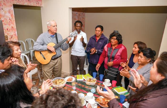 Father Masson, playing the guitar, and Maryknoll Seminarian John Siyumbu (white shirt) meet with Christian communities at Father Masson's home. (Nile Sprague/Bolivia)