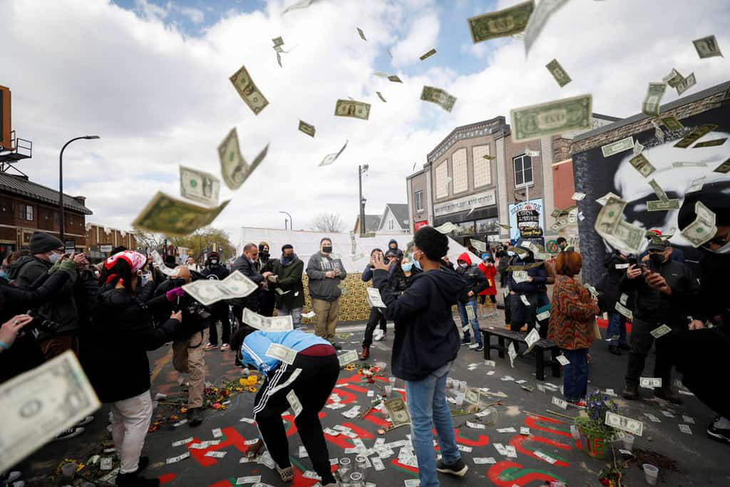 People at George Floyd Square in Minneapolis react with $1 bills April 20, 2021, after jurors issued their verdict convicting former Minneapolis police officer Derek Chauvin of second-degree unintentional murder, third-degree murder and second-degree manslaughter in the death of Floyd. (CNS photo/Octavio Jones, Reuters)