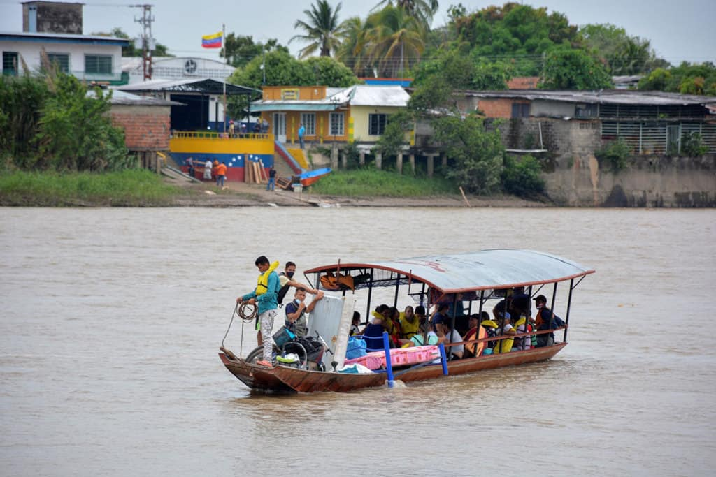 Venezuelan refugees arrive by boat in Arauquita, Colombia, April 5, 2021, after fleeing their country due to a military offensive. Church groups in Colombia are mobilizing to support thousands of Venezuelan refugees who recently fled the military offensive and are now stuck in the remote Colombian border town. (CNS photo/Reuters)