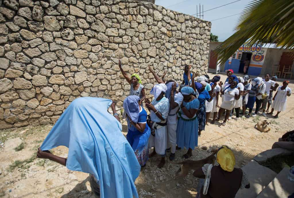 People pray near the Church of St. Roch in Port-au-Prince, Haiti, April 12, 2021. A French priest, two nuns and three laypeople who were abducted together on their way to the parish April 11. (CNS photo/Valerie Baeriswyl, Reuters)