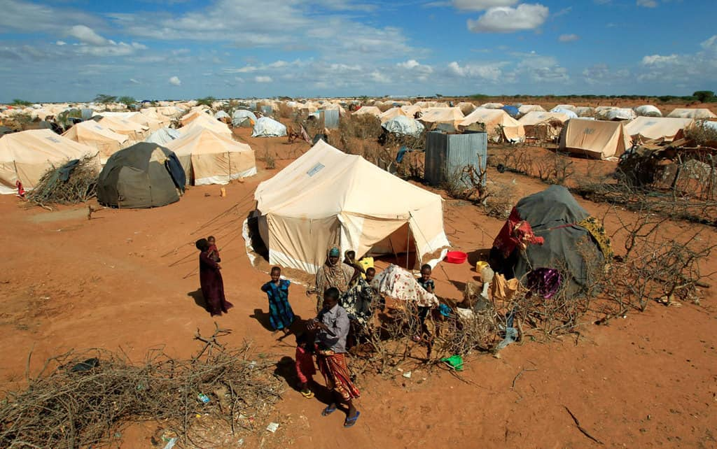 Refugees stand outside their tent in 2011 at a refugee camp in Dadaab, Kenya, across the border from Somalia. Catholic bishops in Kenya are urging the government to shelve plans to close Dadaab and Kakuma refugee camps that host refugees who fled civil war and famine in Somalia and South Sudan. (CNS photo/Thomas Mukoya, Reuters)