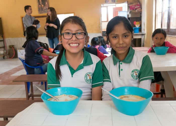 Anahi Perez (left) and Helen Pardo Vivar eat lunch at the after-school tutoring center in Cochabamba, Bolivia, before the country lockdown caused by COVID-19. (Nile Sprague/Bolivia)