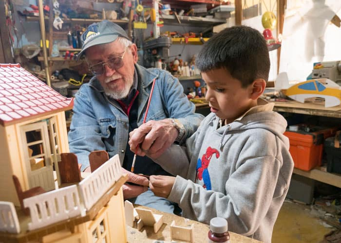 Father Paul Sykora, who runs the after-school tutoring program in Cochabamba, Bolivia, teaches a boy how to paint a toy house. (Nile Sprague/Bolivia)